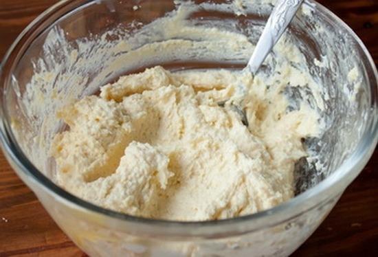 В полученную массу всыпьте еще 100 г сахара и добавьте творог