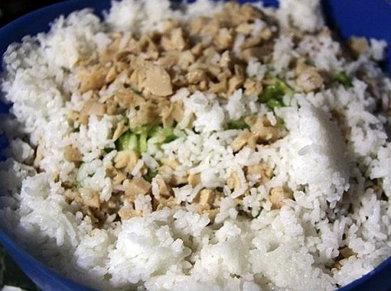 К капусте с огурцами выкладываем мясо кальмаров и рис