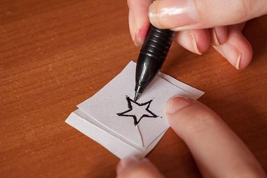 Теперь на втором клочке бумаги обведите вырезанный эскиз татуировки